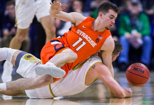 Syracuse's Joseph Girard III(11) competes for a loose ball with Notre Dame's Rex Pflueger during the first half of an NCAA college basketball game Wednesday, Jan. 22, 2020, in South Bend, Ind.