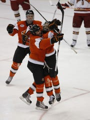 RIT's Cameron Burt, right, celebrates his goal with teammates Chris Tane, left, and Tyler Brenner (behind) in the third period of RIT's 2-1 upset win over Denver University.  Tanev scored RIT's other goal.