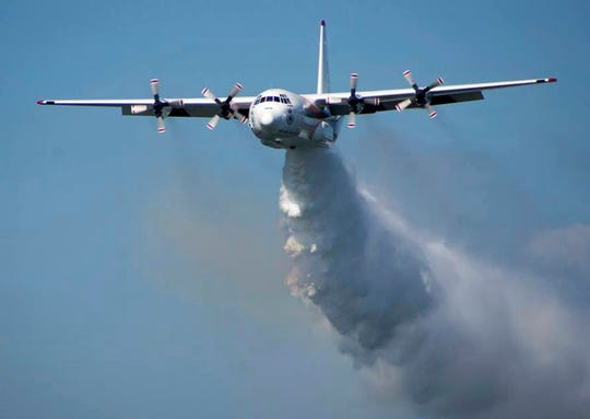 In this undated handout photo from the Rural Fire Service, a C-130 Hercules plane called ÅgThorÅh drops water during a flight in Australia. Officials in Australia on Thursday, Jan. 23, 2020, searched for an tanker believed to have crashed while fighting wildfires.