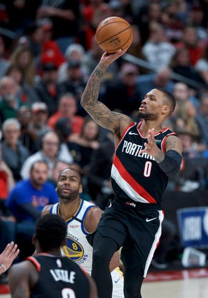 Portland Trail Blazers guard Damian Lillard, right, shoots against the Golden State Warriors during the second half of an NBA basketball game in Portland, Ore., Monday, Jan. 20, 2020.