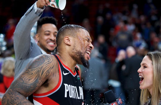 Portland Trail Blazers guard Damian Lillard, center, gets doused by guard CJ McCollum after Lillard scored 61 points against the Golden State Warriors in an NBA basketball game in Portland, Ore., Monday, Jan. 20, 2020. The Trail Blazers won 129-124 in overtime