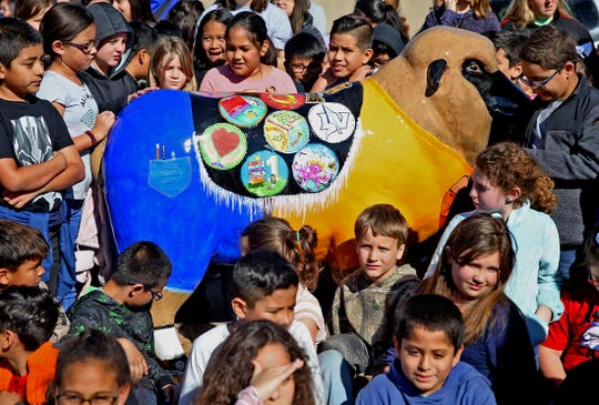Students at Holiman Elementary pose for photos with their new sheep statue Thursday, Jan. 23, 2020.