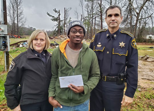 Bossier Sheriff's Office Capt. Doug Lauter and Sgt. Tina Fruge present a check to Tracey Jefferson on his land at Davis Road. Jefferson lived with his great-grandfather, Ira Jefferson, who died from injuries received when a tornado destroyed his home.