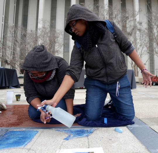 Twin sisters from Rickards High School Imari Still, left, and Amaria Still, 16, work together as the create a masterpiece out of chalk at the Capitol on Thursday, Jan. 23, 2020.