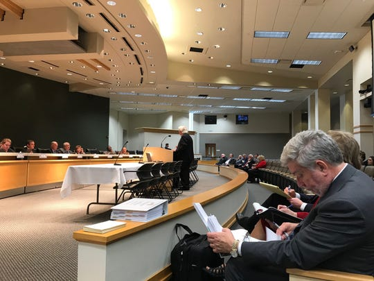 Michael Mattimore, front, lead negotiator for DMS reviews notes, while AFSCME's Hector Ramos, at lectern, speaks to lawmakers about contract negotiations with the State of Florida