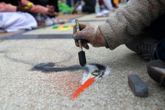 A student uses a sponge brush to blend chalk as they create a work of art outside the Capitol on Thursday, Jan. 23, 2020.
