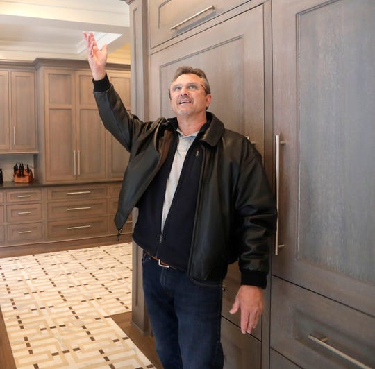 Real estate agent Kevin Davis, with The Naumann Group Real Estate, Inc., motions towards the coffered ceilings inside a multi-million-dollar home located in the Bobbin Trace subdivision.