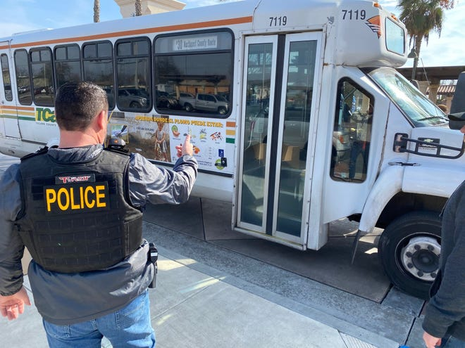 A police officer gestures at the bus a man stole before driving it to the Visalia Transit Center with police in pursuit on Thursday, Jan. 23.