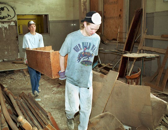 Matthew Smith, left, and his brother, Donnell, remove some old, broken furniture from the lobby of the old Holt Hotel, in April 2001. Matthew  headed up a project to clean up the first and second floor of the building as an Eagle Scout Project. The hotel was built in 1910 and had been vacant for 25 years.