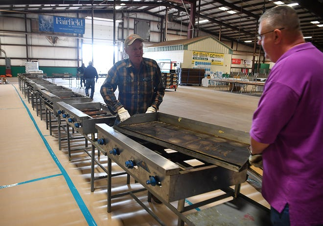 John Rhoads, left, and Scott Ermis set up one of many griddles that will be used to cook thousands of pancakes and thousands of sausage patties for the 64th Annual University Kiwanis Club Pancake Festival at the Bridwell Ag Center.