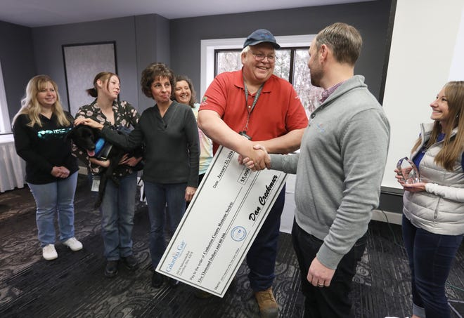Larry WIlkin gets a handshake from Columbia Gas of Ohio President and COO Dan Creekmur after Wilkin was named the company's 2019 volunteer of the year during a ceremony at EagleSticks Golf Club on Thursday. With them are Wilkin's wife, Barb, and representatives from the Coshocton County Humane Society, including Scooter, a dog with two legs who is up for adoption.