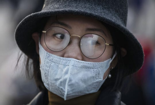 A Chinese woman's glasses fog up while wearing a protective mask at Beijing Station before she boarded a train before the annual Spring Festival on January 22, 2020 in Beijing, China. The number of cases of a deadly new coronavirus rose to over 400 in mainland China Wednesday.