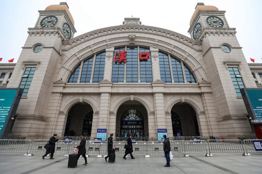People pass by the closed Hankou Railway Station in Wuhan, central China's Hubei province Thursday. Wuhan has shut down public transportation, including railway stations, the airport, bus and subway services, in the municipality to control the spread of the new coronavirus.