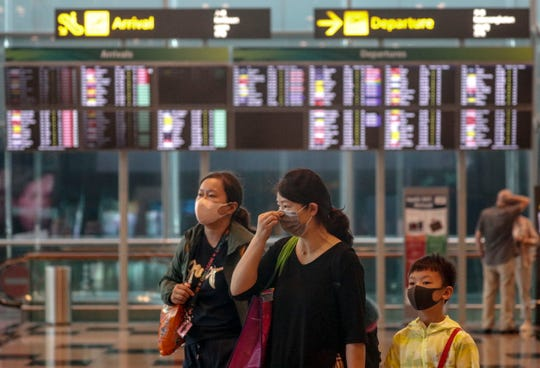 A mother and her children are seen wearing masks while walking through Singapore's Changi Airport  Thursday. The airport has expanded temperature screenings for all travelers on flights arriving from China.