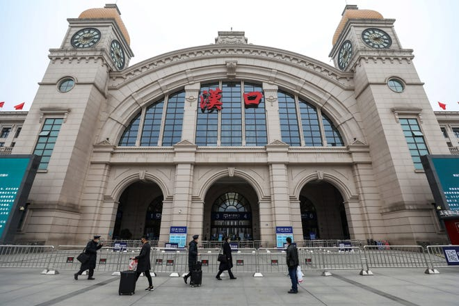 People pass by the closed Hankou Railway Station in Wuhan, central China's Hubei province,  January 23, 2020.