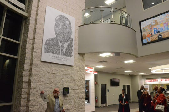 Richard Schlatter stands below a portrait of Dr. Martin Luther King, Jr. now displayed in the lobby of the Battle Creek Police Department.
