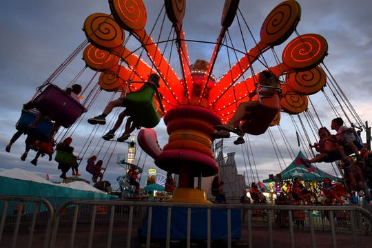 Visitors ride swings on the midway during the 2019 New York State Fair.