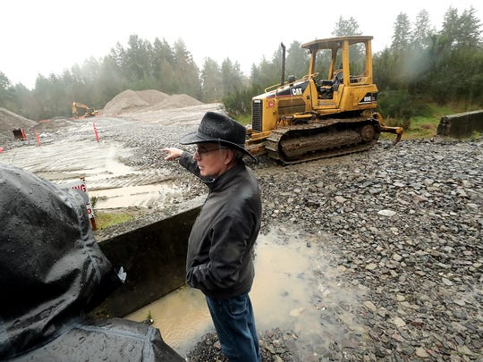 Mike Sherry gestures toward the sand mine site off of Bainbridge Island's Fletcher Bay Road as he talks about neighborhood concerns about the environmental impacts of the site on Thursday, Jan. 23, 2020.