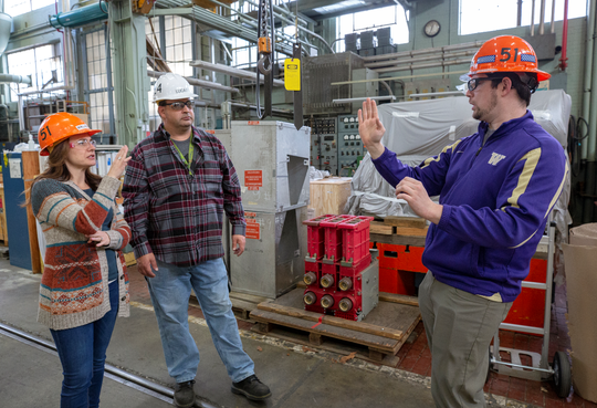 Brandon Salley, right, talks with a colleague through interpreter Marlene Bell, left, inside Shop 51, the electricians' home at the Puget Sound Naval Shipyard. Salley, 30, recently became the first person who is deaf to be able to operate a crane within the shop.