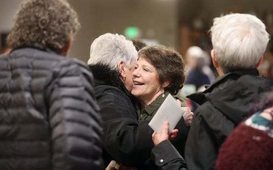 Denise Agee hugs well-wishers during a gathering in honor of her retirement after 30 years of service at St. Vincent de Paul.