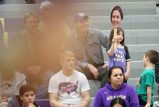Mazie Beaudoin holds up a cutout of her sister Holly during North Kitsap's wrestling match on Thursday, Jan. 23, 2020.