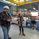 Brandon Salley, right, talks with a colleague through interpreter Marlene Bell (center) inside Shop 51, the electricians home at the Puget Sound Naval Shipyard. Salley, 30, recently became the first person who is deaf to be able to operate a crane within the shop.