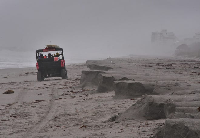Brevard County Ocean Rescue lifeguards drive past eroded sand Thursday afternoon at HowardE.FutchMemorial Park at Paradise Beach near Indialantic.