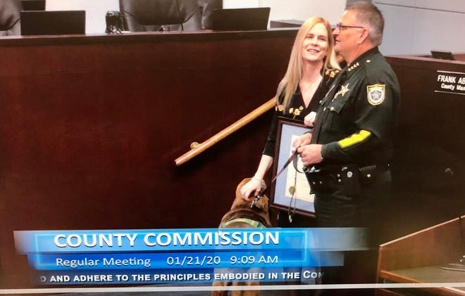 Brevard County Commissioner Kristine Isnardi, Sheriff Wayne Ivey and Brevard County Sheriff's Office bloodhound/mascot Junny prepare for a photo in conjunction with passage of a resolution  sponsored by Isnardi in support of the principles embodied by the U.S. Constitution.