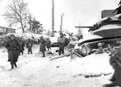 """Members of the 117th Infantry Regiment, 30th Infantry Division, move past a destroyed American M5 """"Stuart"""" tank on their march to capture the town of St. Vith at the close of the Battle of the Bulge."""