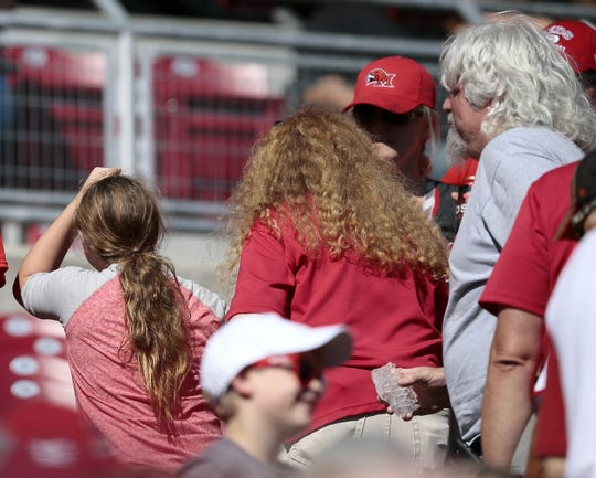 A young girl is walked from her seat after being hit in the head by foul ball in the bottom of the first inning of the MLB National League game between the Cincinnati Reds and the St. Louis Cardinals at Great American Ball Park in downtown Cincinnati on Saturday, Sept. 3, 2016.  After three innings, the Reds and Cardinals were tied 1-1.