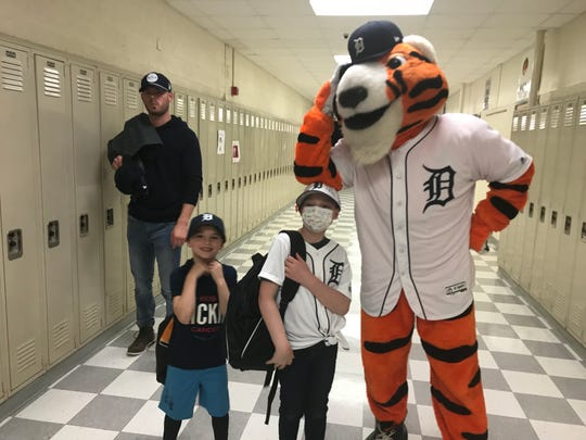 Brinley Jungnitsch, 9, middle, poses with the Detroit Tigers mascot, Paws, during the team's winter caravan stop at St. Clair Shores Lake Shore High School on Thursday, Jan. 23, 2020.