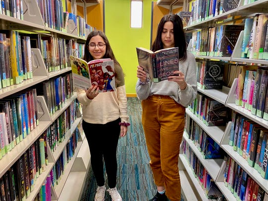 Founders of Girls of the Crescent: Zena Nasir (right) reads 'The Lines We Cross' and Mena Nasiri (left) reads 'Ms. Marvel' as they pose for a photo at the Rochester Hills Public Library.