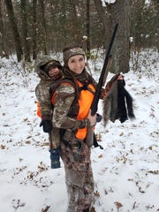 Heather Iverson carries her son, 3, on her back during a squirrel hunt.