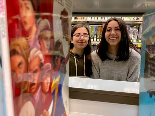 Founders of Girls of the Crescent, Zena Nasir (right) and Mena Nasiri (left), pose for a photo near one of their favorite books, 'Ms. Marvel' at the Rochester Hills Public Library.