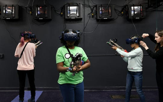 VR+ Zone program manager Bree Malvin, 25, right, adjusts the headset on Azalia O'Hara, 11, while Kelly O'Hara, left, both of Detroit and Angela-Marie McFadden, 10, of Detroit get used to wearing a VR headset.