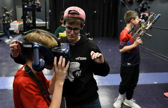 VR+ Zone general manager Grace Fowler, center, adjusts the VR helmet on Will Qualman, 11, left, before the group starts to play at VR+ Zone in Ferndale, Mich. on Jan. 15, 2020.