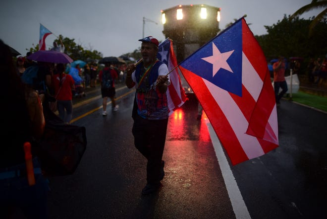 A man sells Puerto Rican flags under the rain during a protest organized by Puerto Rican singer Rene Perez of Calle 13 over emergency aid that until recently sat unused in a warehouse amid ongoing earthquakes, in San Juan, Puerto Rico, Thursday, Jan. 23, 2020.