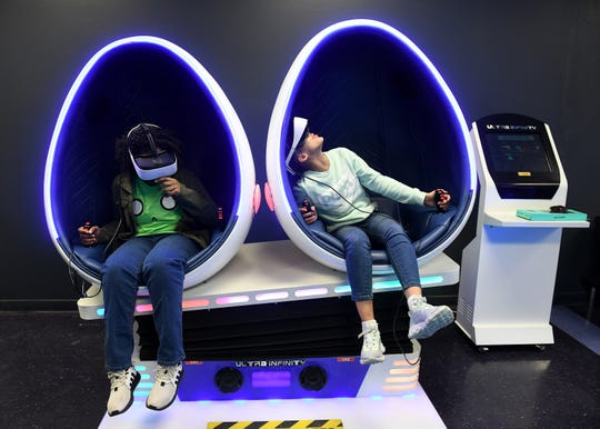 Angela-Marie McFadden, 10, left, and her friend, Azalia O'Hara, 11, both of Detroit play a ride simulation game while having Angela-Marie's birthday party at VR+ Zone in Ferndale, Mich. on Jan. 15, 2020.  VR+ Zone is equipped with HTC VIVE Pro Headsets and the latest NVIDIA Graphic Card which provide high definition graphics and deliver an immersive gaming experience.