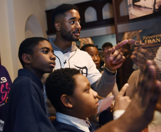 """Niko Goodrum points to a clue with team members, from left, Nathaniel Collins, 12, and Ian Polk, 11, during an informational treasure hunt inside  the """"And Still We Rise"""" exhibit at the Charles H. Wright Museum of African American History in Detroit."""