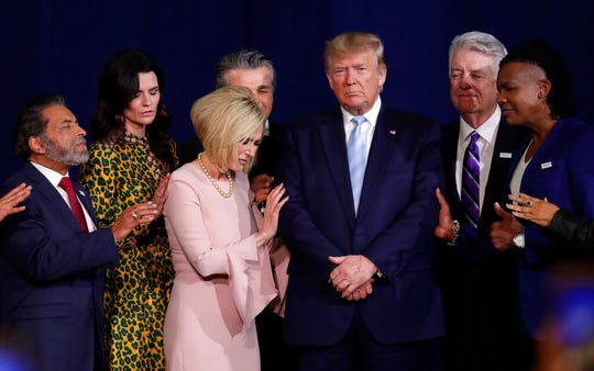 In this Jan. 3, 2020, file photo, faith leaders pray with President Donald Trump during a rally for evangelical supporters at the King Jesus International Ministry church in Miami.