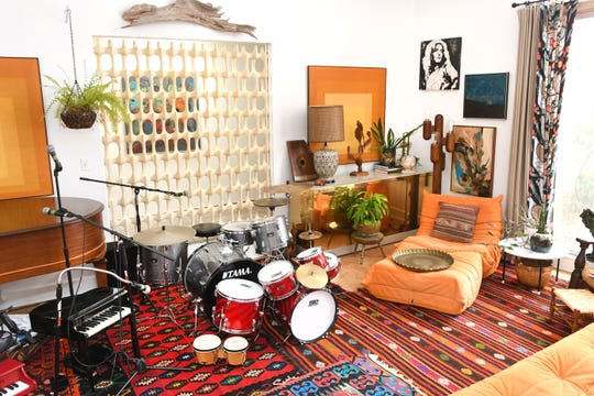 The colorful sunken living room of the Elliott family displays an adult and children's drum set.