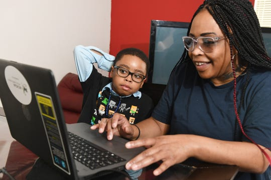 Ryan Cargile, 9, prepares for his Michigan Charter Virtual Academy lesson with his mother Ebony Cargile at their Flint home. Ryan Cargile left the Flint schools special education program after a bad experience, now he works with online classes with his mother.