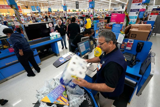 Walmart associate Javaid Vohar, right, checks out customers at a Walmart Supercenter in Houston.
