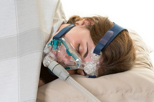 A woman wears a CPAP mask for treating sleep apnea, which is a type of sleep disorder characterized by pauses in breathing or instances of shallow or infrequent breathing during sleep.