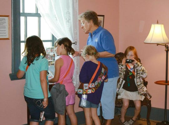 Guest lighthouse keeper Carol Garlo leads a group of school children on a tour of the keepers quarters at the Tawas Point Lighthouse.