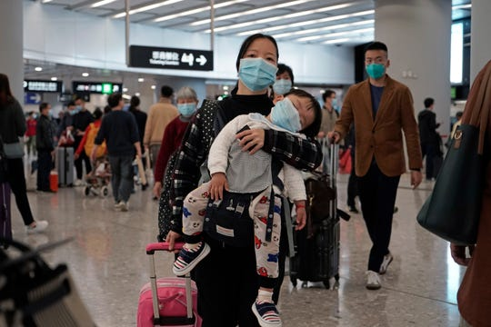 Passengers wearing protective face masks enter the departure hall of a high speed train station in Hong Kong, Thursday, Jan. 23, 2020.