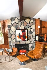 The main living room with rock fireplace and exposed wood beans and tilt in bar at the Elliott family home.