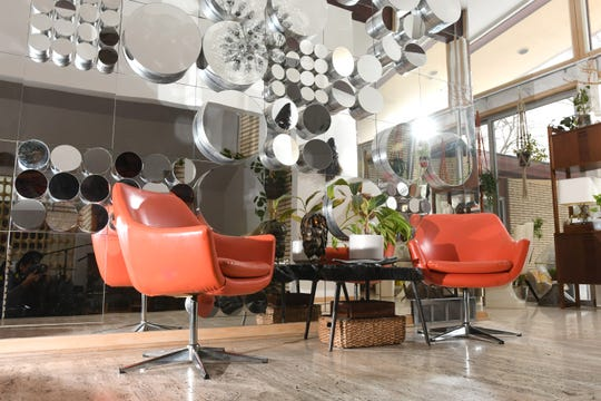 A 1960's multi angled mirror wall is framed by two orange chairs at the Elliott family home in Southfield on Thursday, January 23, 2020.