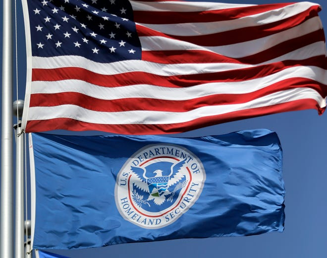 FILE - In this July 31, 2014 file photo, the U.S. and U.S. Department of Homeland Security flags fly in Karnes City, Texas.  T