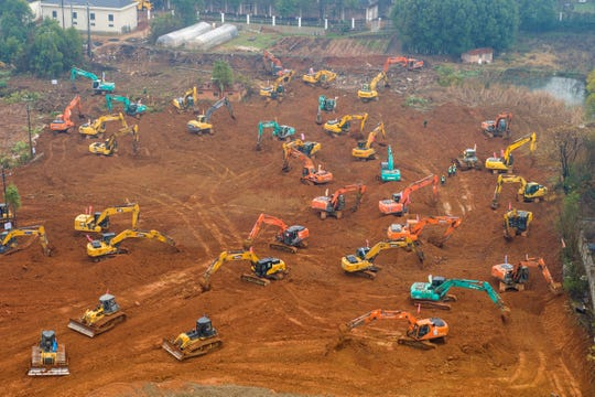 Heavy equipment works at a construction site for a field hospital in Wuhan Friday.